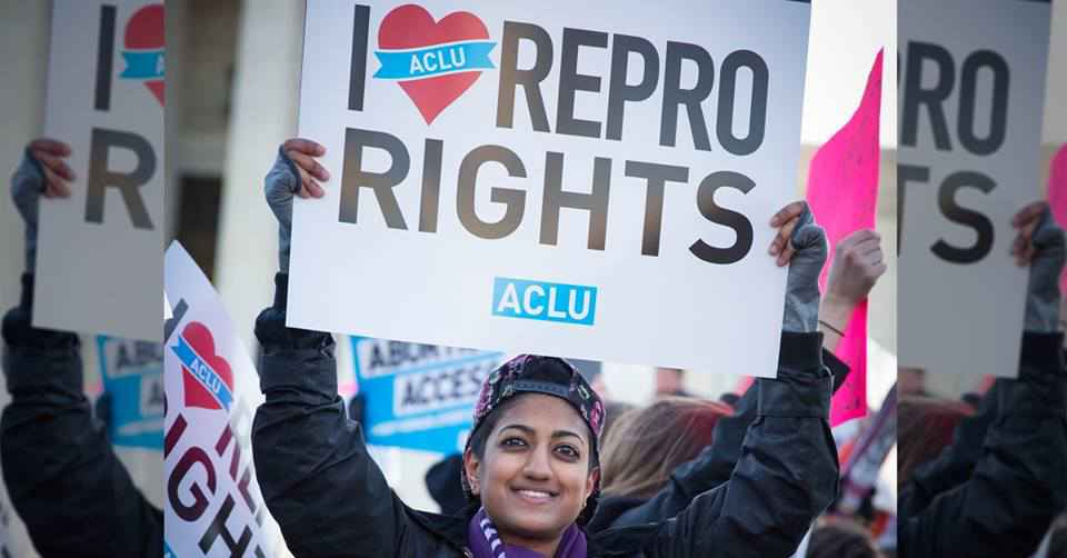 Person holding protest sign that says I (heart) REPRO RIGHTS and ACLU logo