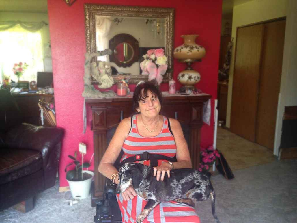 A woman sitting in a wheel chair with her dog on her lap in her house